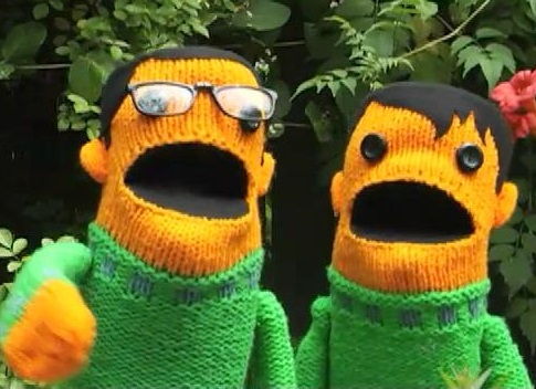 Knit orange hand puppets in matching green sweaters.